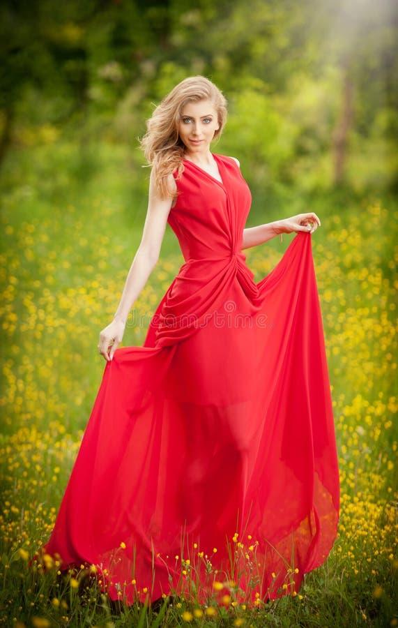 穿一身长的红色庄重装束的年轻美丽的白肤金发的妇女画象摆在一个绿色草甸 时兴性感有吸引力 免版税库存图片