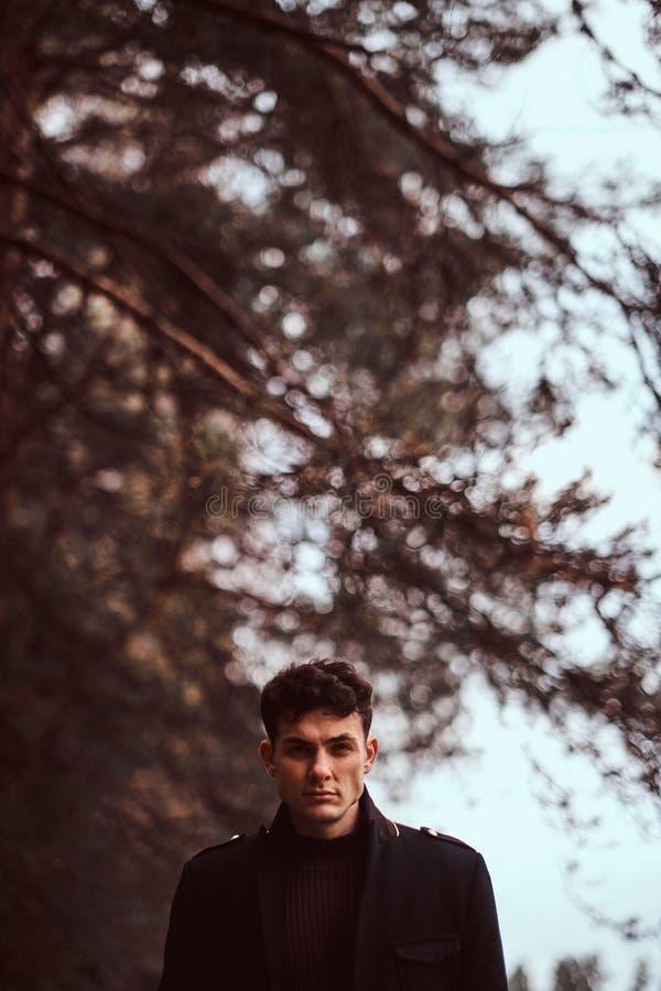 穿一黑色大衣的年轻人在秋天森林里 库存照片