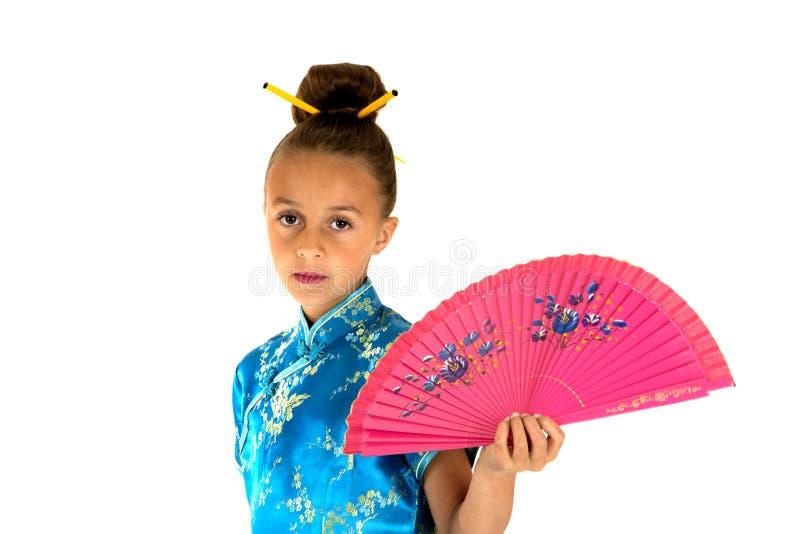 穿一件亚洲礼服的美丽的女孩拿着一个桃红色爱好者 库存照片