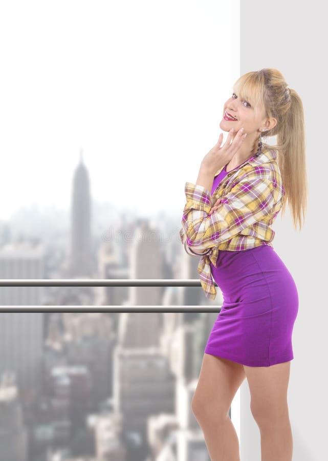穿一件性感的紫色礼服的少妇 免版税图库摄影