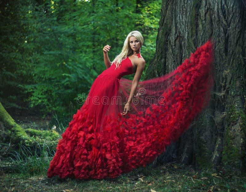 穿一件惊人的红色褂子的美丽的妇女 图库摄影