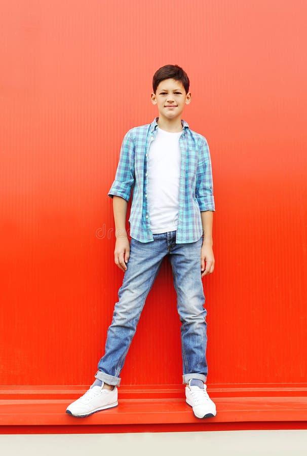 穿一件方格的衬衣和牛仔裤的漂亮的孩子男孩 库存图片