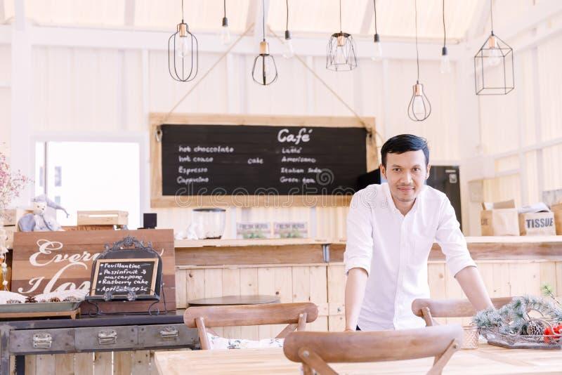 穿一件白色衬衣的亚裔人站立在面包店商店 库存图片