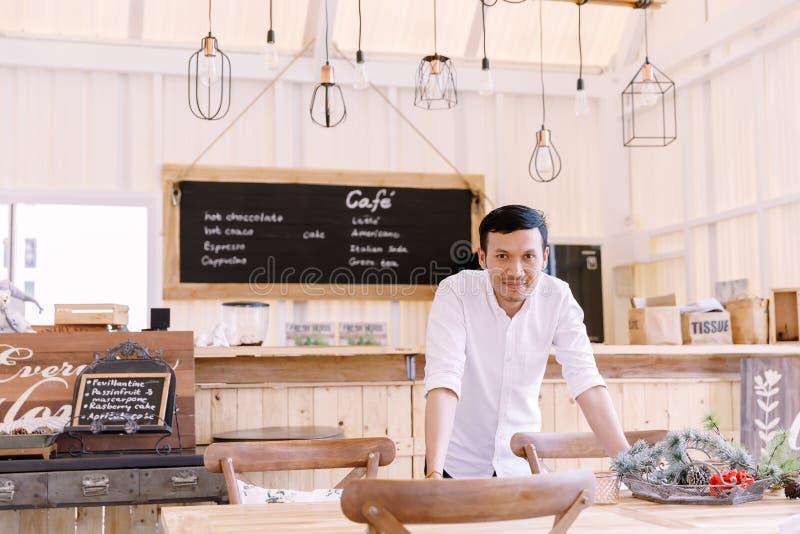 穿一件白色衬衣的亚裔人站立在面包店商店 免版税库存图片