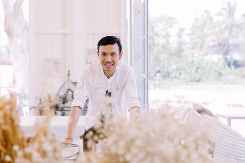 穿一件白色衬衣的亚裔人站立在面包店商店 免版税库存照片