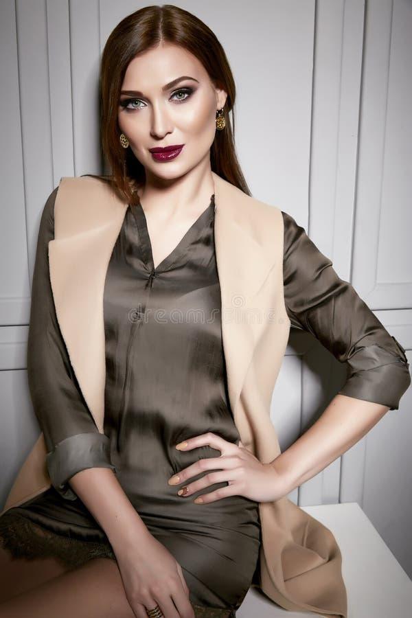 穿一件短的丝绸礼服时髦的设计和时兴的夹克的美丽的年轻性感的深色的妇女,米黄脚跟稀薄长期穿上鞋子 免版税库存照片
