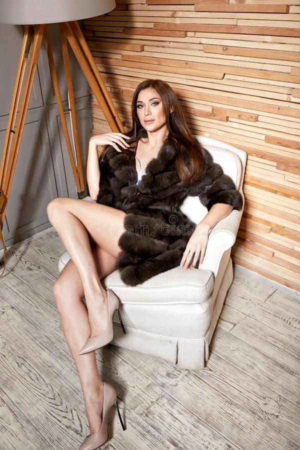穿一件短的礼服时髦的设计和时兴的皮大衣的美丽的年轻性感的深色的妇女,米黄脚跟穿上鞋子长的稀薄的腿 免版税库存照片