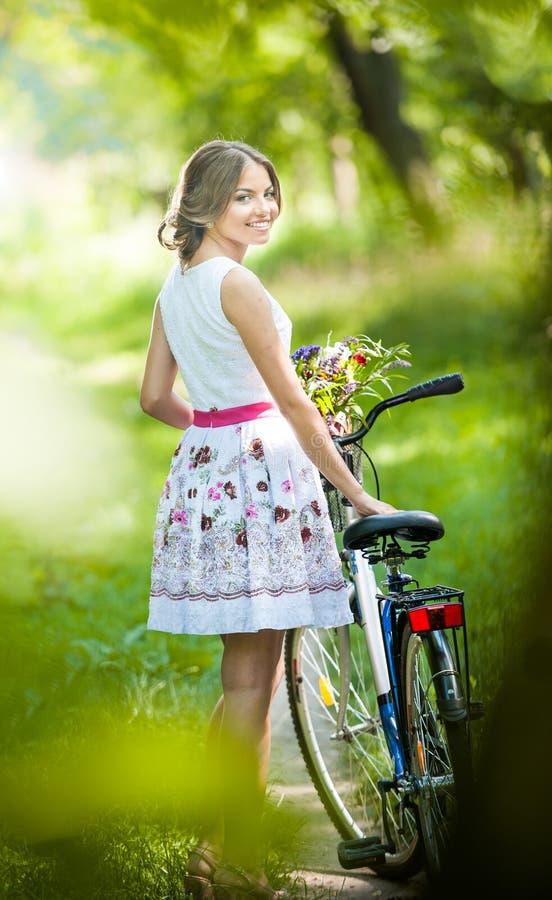 穿一件精密白色礼服的美丽的女孩获得乐趣在有自行车的公园。健康室外生活方式概念。葡萄酒风景 免版税图库摄影