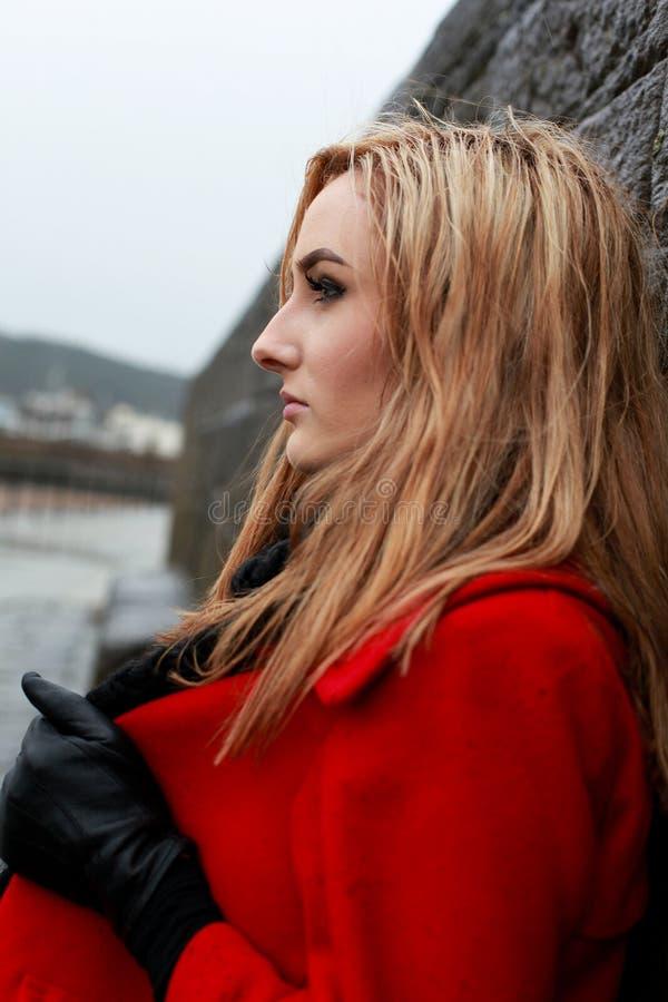 穿一件红色外套的一个少妇的档案 免版税库存图片