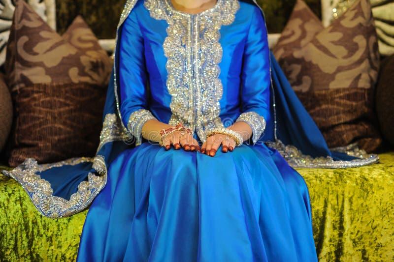 穿一件蓝色礼服的新娘坐法坛,朝向没看见 库存图片