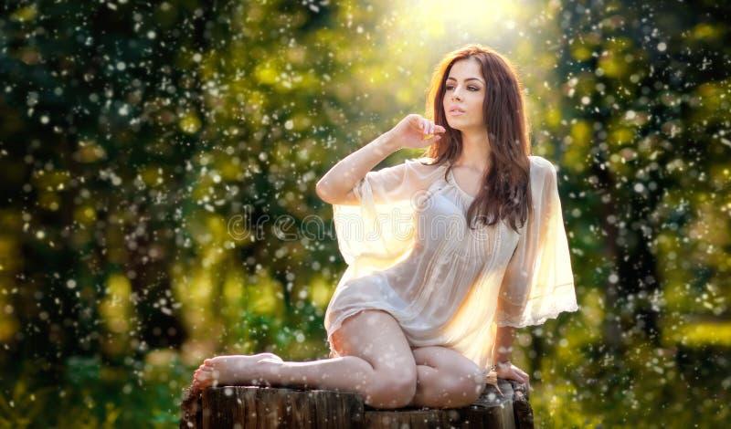 穿一件透明白色女衬衫的年轻美丽的红色头发妇女摆在一个绿色森林时兴的性感的女孩的一个树桩 免版税库存照片