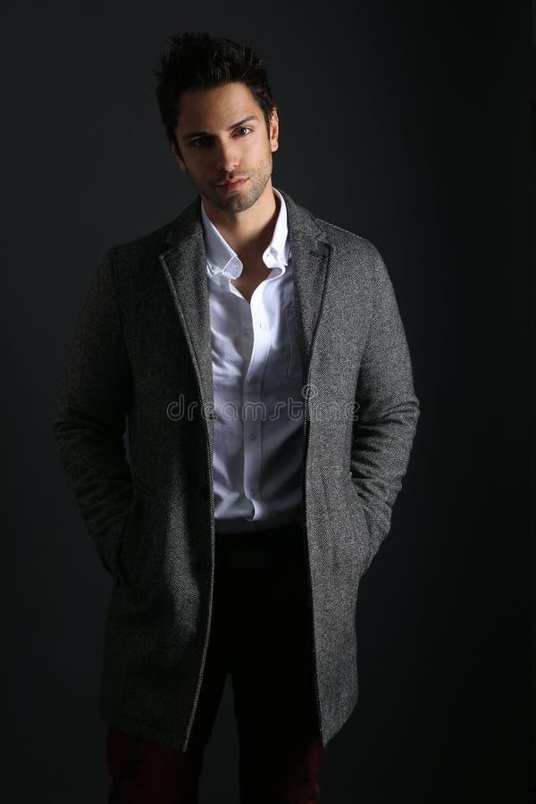 穿一件长的外套的英俊的人 库存照片