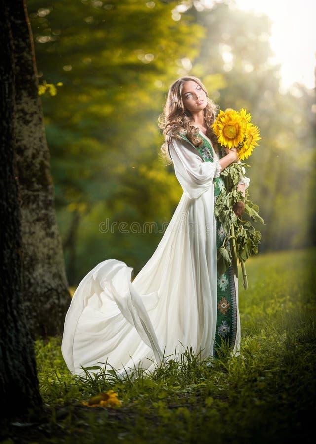 穿一件长的白色礼服的少妇拿着向日葵室外射击。美丽的白肤金发的女孩画象有黄色花的 免版税库存图片
