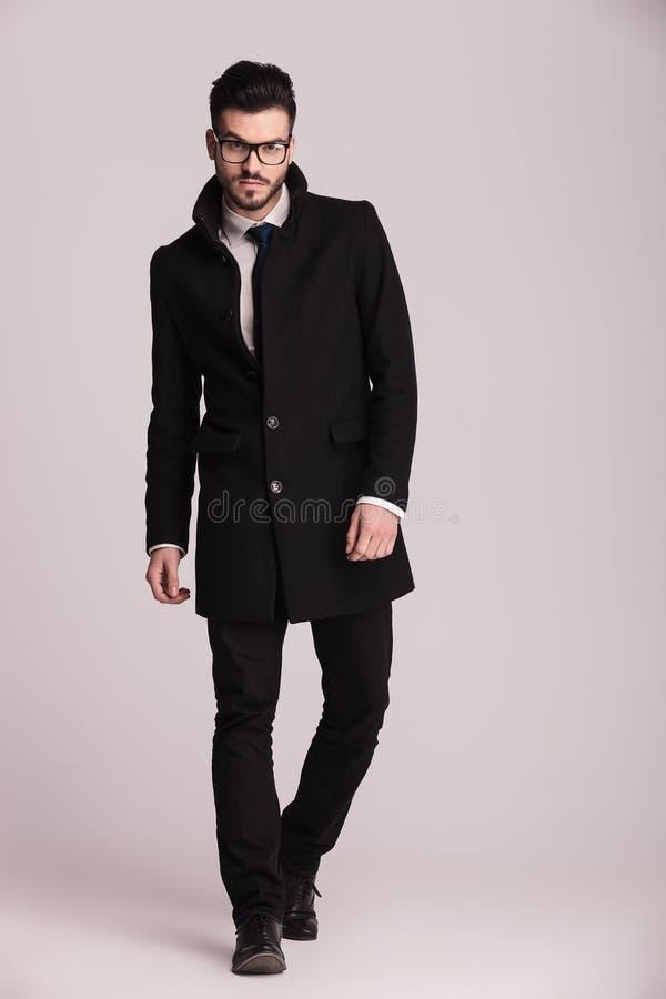 穿一件长的黑外套的英俊的年轻商人 免版税库存照片