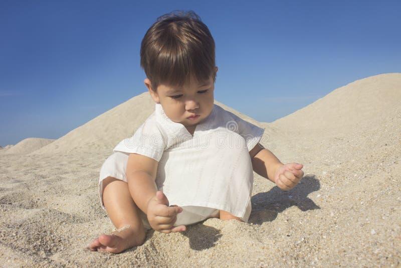 穿一件阿拉伯礼服的男孩使用在沙丘中的沙子 库存图片