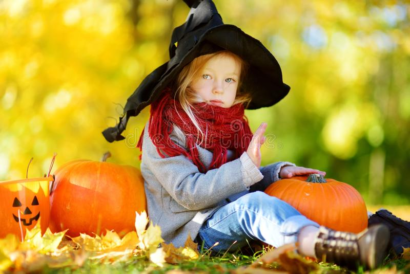 穿万圣夜服装的可爱的小女孩获得在一个南瓜补丁的乐趣在秋天天 库存图片