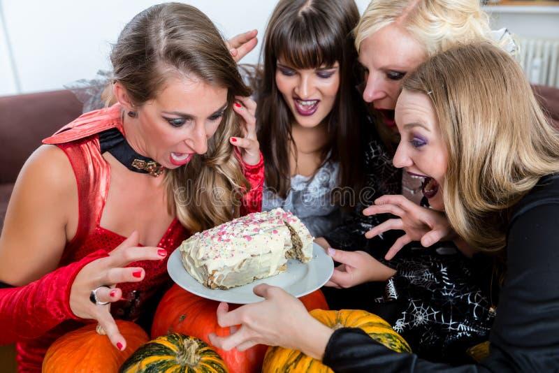 穿万圣夜服装的四名妇女,当摆在滑稽以前时 免版税图库摄影