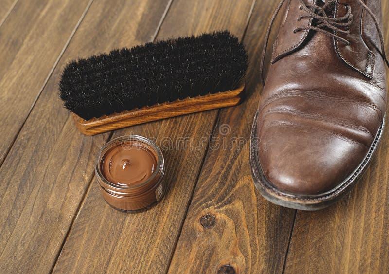 穿上鞋子清洁产品并且在一双肮脏的棕色鞋子旁边掠过 库存照片