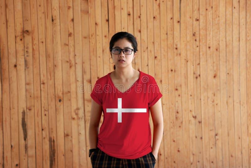穿丹麦旗子颜色衬衣和站立用在裤兜的两只手的妇女在木墙壁背景 免版税图库摄影