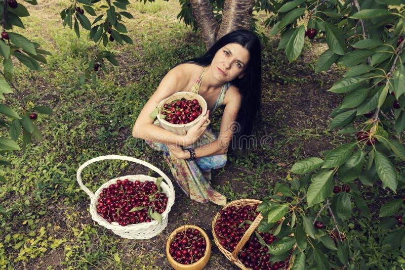 穿五颜六色的礼服的美丽的年轻女人在与两个柳条筐和两个桶的cherriy树下有很多果子 免版税库存照片