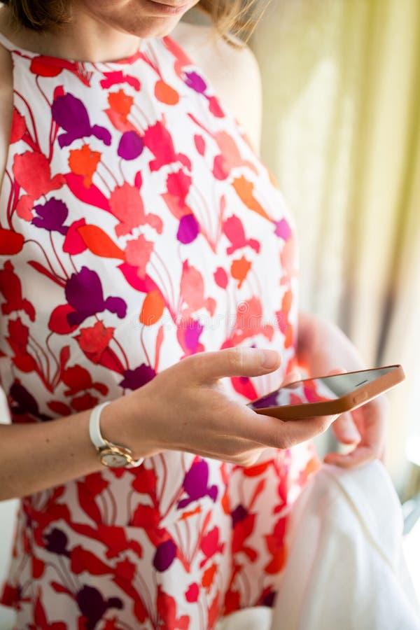 穿五颜六色的衣裳的典雅的法国妇女使用智能手机 图库摄影