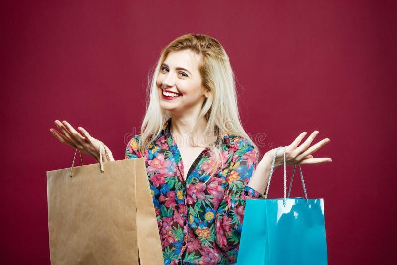 穿五颜六色的衬衣的欢悦女性顾客特写镜头画象拿着在桃红色背景的购物袋 愉快的女孩 库存图片