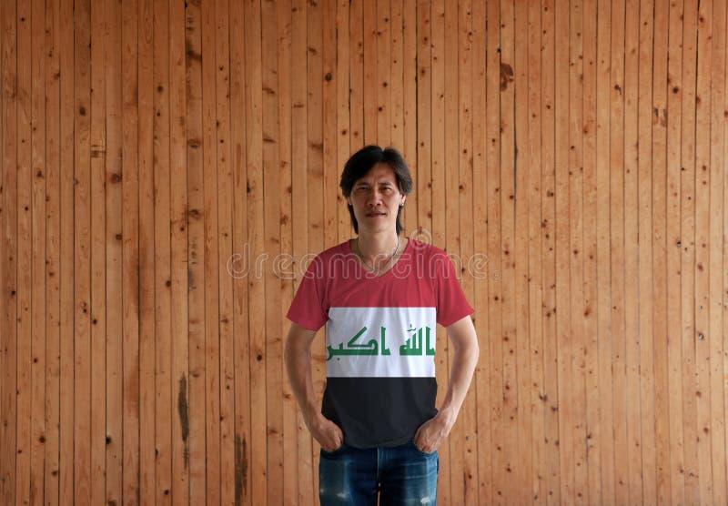 穿伊拉克旗子颜色衬衣和站立用在裤兜的两只手的人在木墙壁背景 免版税库存照片