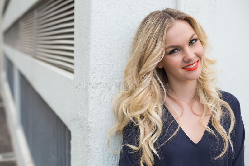穿优等的礼服的微笑的可爱的金发碧眼的女人户外 免版税库存照片