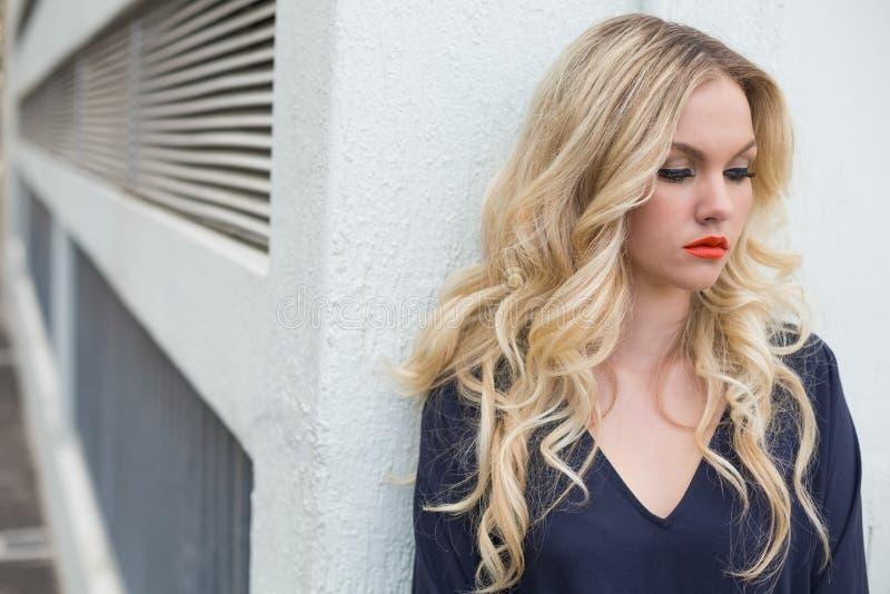 穿优等的礼服的沉思可爱的金发碧眼的女人户外 免版税库存照片