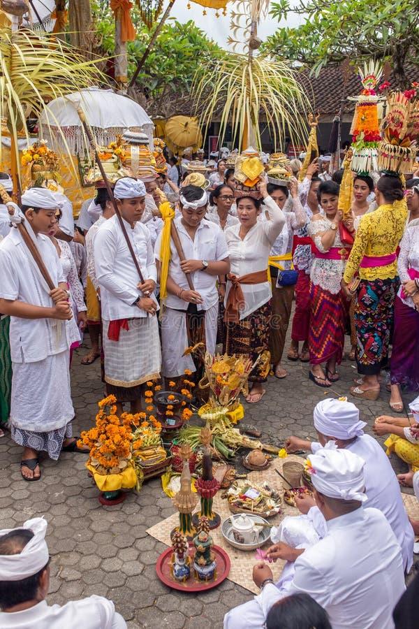 穿传统印度尼西亚衣裳的未认出的当地人民在印度寺庙的传统巴厘语仪式参与 免版税库存照片