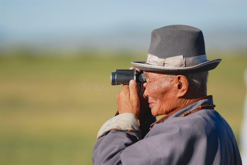 穿传统服装的资深蒙古人在Kharkhorin,蒙古观察与双眼的周围的干草原 库存照片