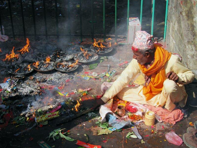 穿传统礼服的尼泊尔人在Pharping,尼泊尔烧在Dakshinkali印度寺庙的蜡烛 免版税库存图片