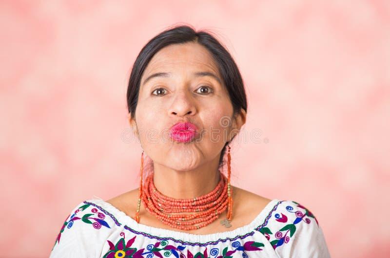 穿传统安地斯山的衣物的特写美丽的西班牙母亲,做亲吻嘴唇对照相机,桃红色演播室 免版税库存照片