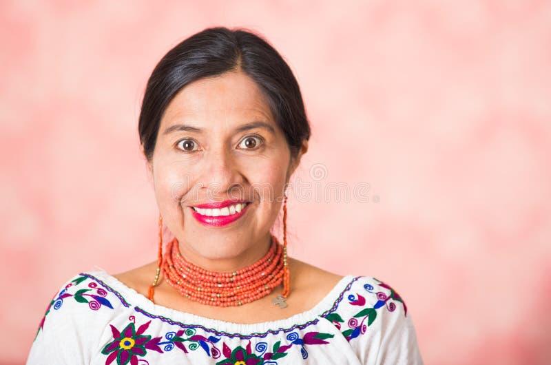 穿传统安地斯山的衣物的特写美丽的西班牙母亲,愉快地摆在,当微笑对照相机,桃红色时 免版税库存图片
