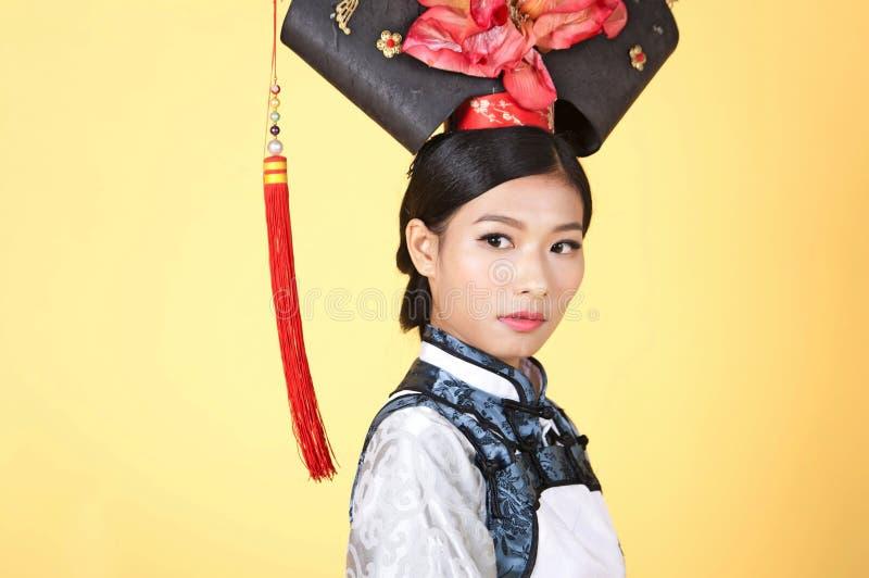 穿传统服装的美丽的中国妇女反对黄色背景 免版税图库摄影
