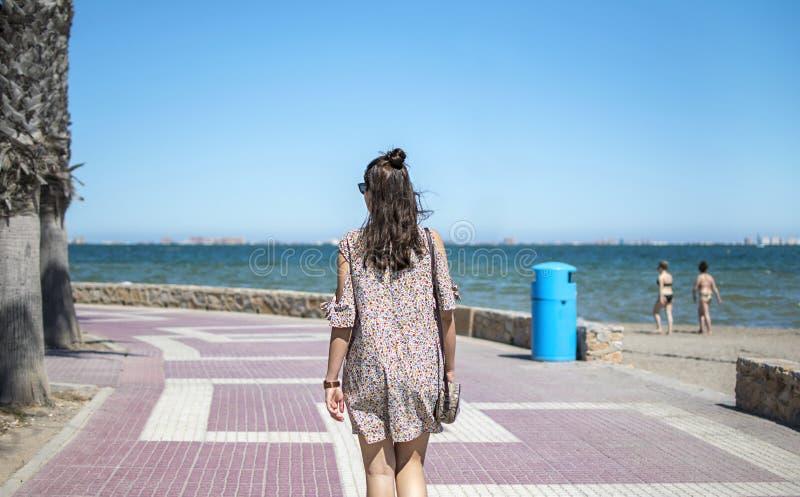 穿便服的愉快的年轻女人走在海滩 免版税图库摄影