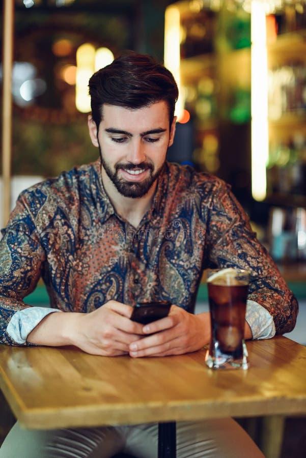 穿便衣的年轻有胡子的人看他的smartpho 免版税库存照片