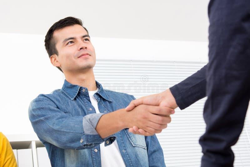 穿偶然斜纹布衬衣的英俊的人做在o的握手 库存图片