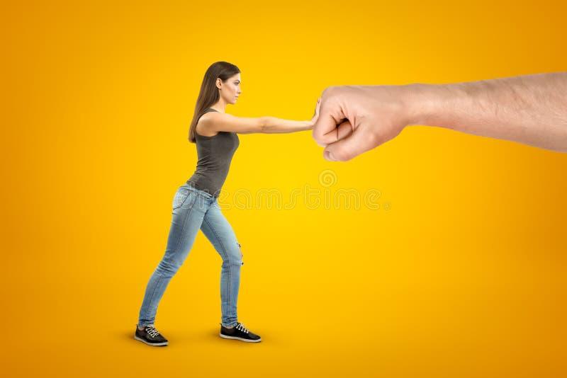 穿偶然牛仔裤和T恤杉的年轻深色的女孩做中止姿态反对大男性舒展了在黄色的拳头 皇族释放例证