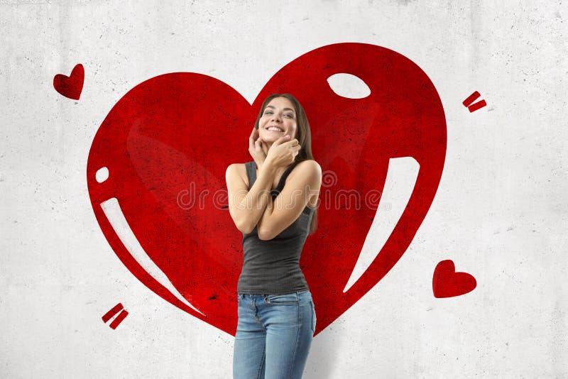穿偶然牛仔裤和T恤杉的年轻深色的女孩微笑和接触与在白色墙壁上画的大红心的面孔 皇族释放例证