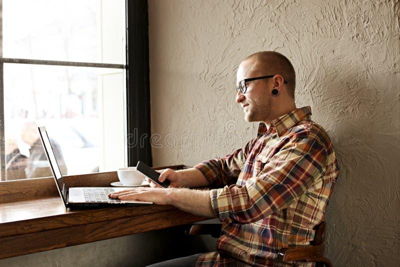 穿偶然行家衣物的微笑的有胡子的商人使用膝上型计算机和细胞智能手机在coffe房子里 库存图片