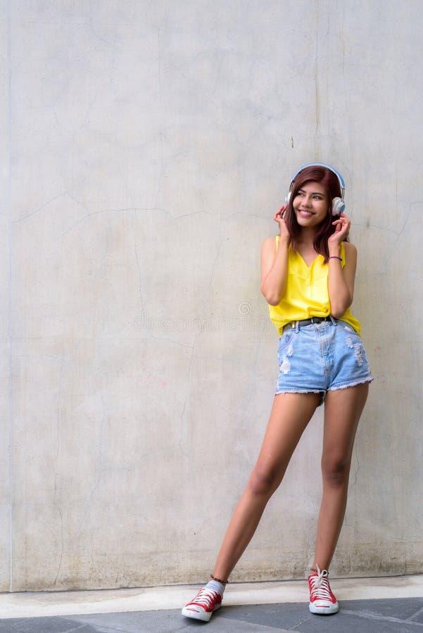 穿充满活力的黄色衬衣的美丽的少年女孩 库存照片