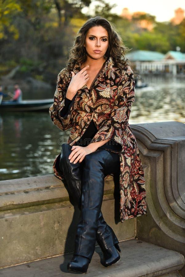 穿典雅的外套的美丽和肉欲的女孩摆在秋天湖旁边在公园 免版税库存照片