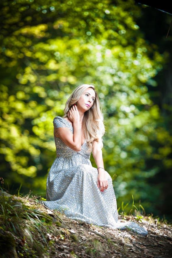穿典雅的白色礼服的可爱的小姐享受神圣光射线在她的面孔的在被迷惑的森林。相当白肤金发 免版税库存照片