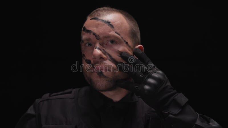 穿军服的英俊的战士画象,被绘他的在黑背景的面孔 股票 人军人赞许 库存图片