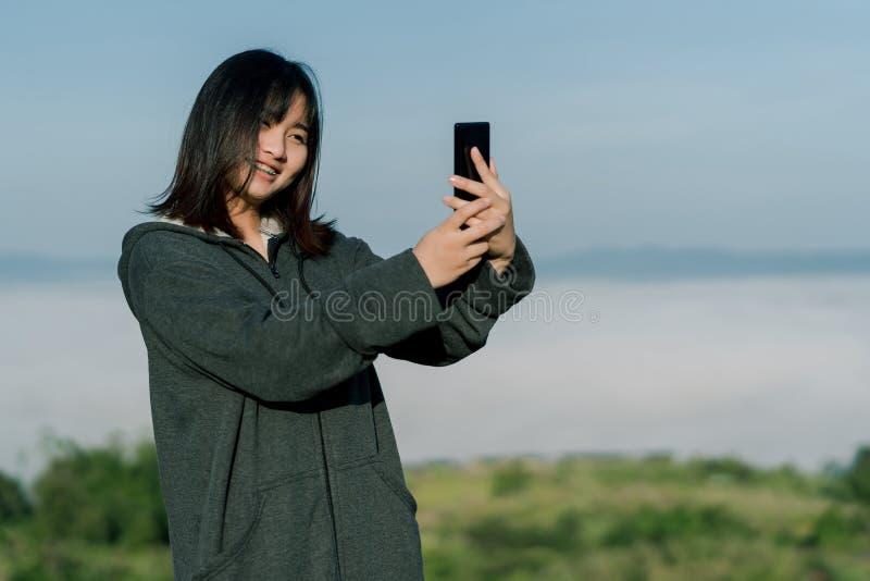 穿冬天夹克的亚裔妇女,在旅游区采取selfie电话,在雾和山后拍照片与a 免版税库存图片