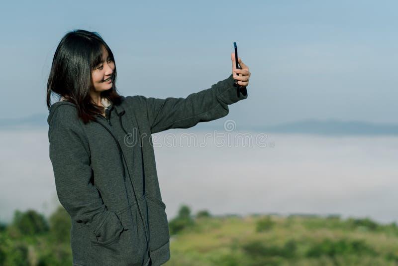穿冬天夹克的亚裔妇女,在旅游区采取selfie电话,在雾和山后拍照片与a 图库摄影