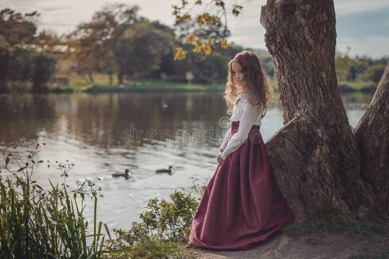 穿减速火箭的衣裳的逗人喜爱的矮小的白种人女孩 美丽的葡萄酒礼服的好女孩 免版税库存照片