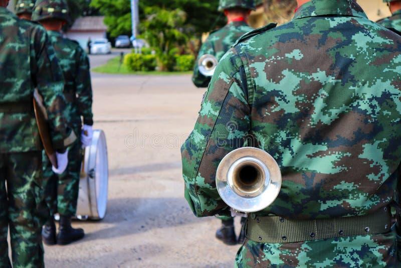 穿制服的一位年轻战士,拿着喇叭仪器,站立,转回去作为背景影像 免版税库存图片