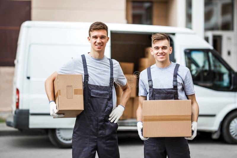穿制服的两名年轻英俊的微笑的工作者在搬运车拿着在他们的箱子旁边充分站立箱子 免版税图库摄影
